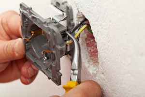 Electrician hands installing wires into electrical outlet - closeup